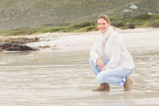 Woman crouching at the shore