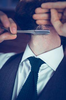 Midsection of man shaving beard