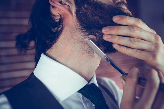 Man shaving beard with razor