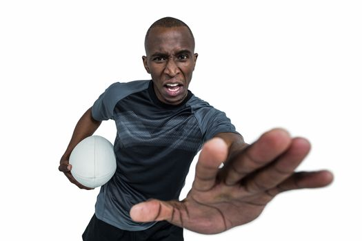 Portrait of sportsman with rugby ball gesturing while defending