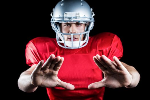 Portrait of sportsman defending while playing American football
