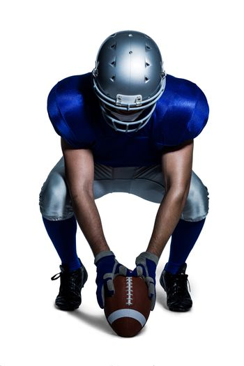 American football player in uniform holding ball while crouching