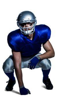 American football player in uniform crouching