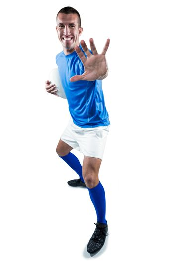 Full length portrait of happy rugby player defending