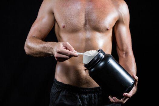 Shirtless man scooping up protein powder