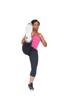 Fit woman kicking to camera