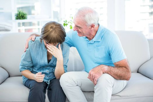 Father consoling pregnant worried daughter while sitting on sofa at home