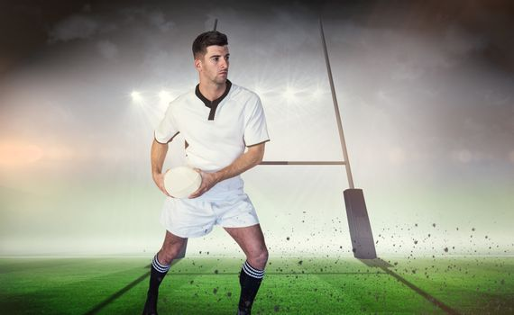 Composite image of rugby player defending with the ball