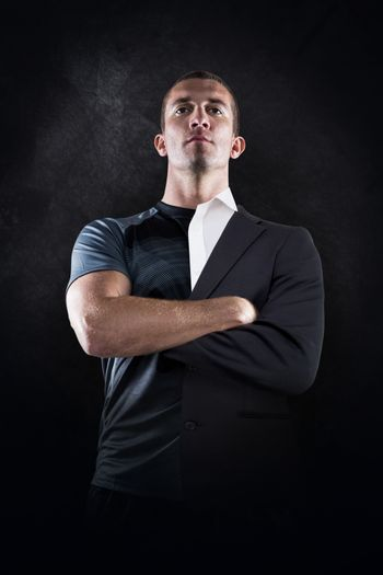 Confident rugby player with arms crossed against half a suit