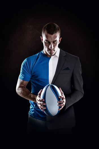 Rugby player holding ball against half a suit