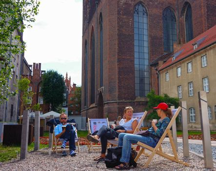 GDANSK, POLAND - JULY 29, 2015: People relaxing on sun chairs at the city center