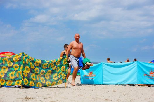 SIANOZETY, POLAND - JULY 22, 2015: People walking on beach sand on a sunny day