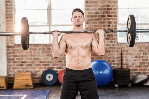 Muscular serious man doing weightlifting