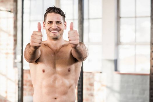 Muscular man standing in front of the camera with his thumbs up in crossfit gym