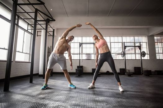 Two fit people doing fitness in crossfit gym