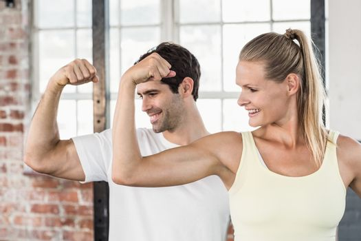 Couple flexing muscles at the gym