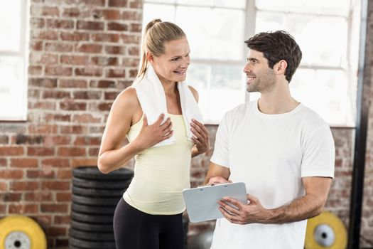 Woman discussing her performance on clipboard with trainer in crossfit gym