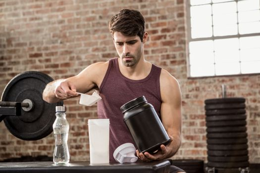 Man adding supplement from tin to bottle