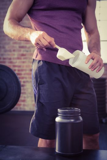 Midsection of man putting supplement into bottle