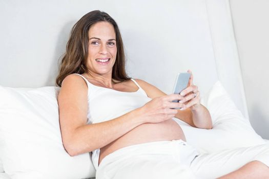 Portrait of woman using mobile phone sitting on bed