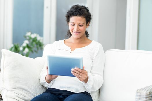 Happy pregnant woman using tablet computer on sofa
