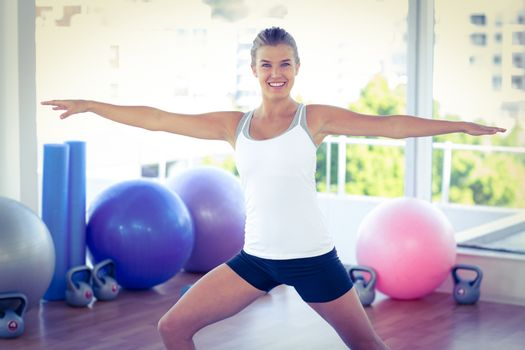 Portrait of a beautiful woman with arms outstretched in fitness studio