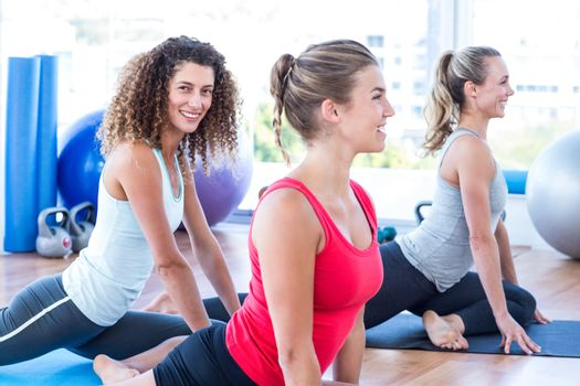 Women smiling while doing pigeon posture