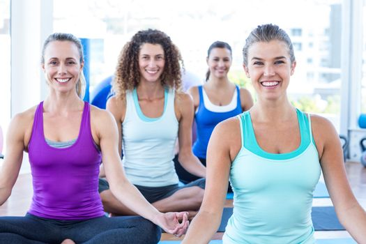 Women smiling while doing easy pose in fitness studio