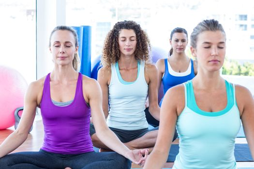 Cropped image of women doing easy pose in fitness center