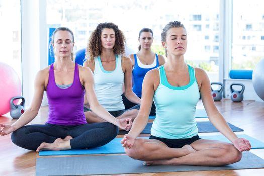 Women in fitness studio doing easy pose