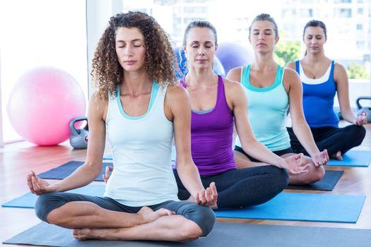 Fit women doing easy pose in fitness studio