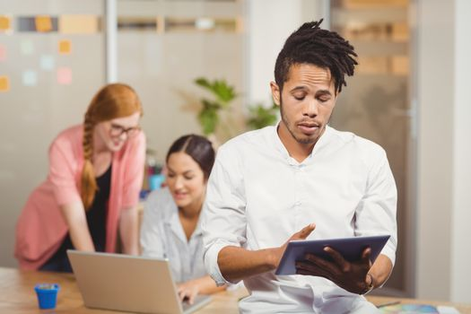 Businessman using digital tablet in office with female colleagues working in background