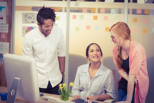 Smiling businesswomen with male colleague at desk in office during meeting