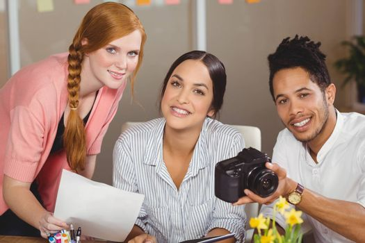 Portrait of smiling business people with camera working in office