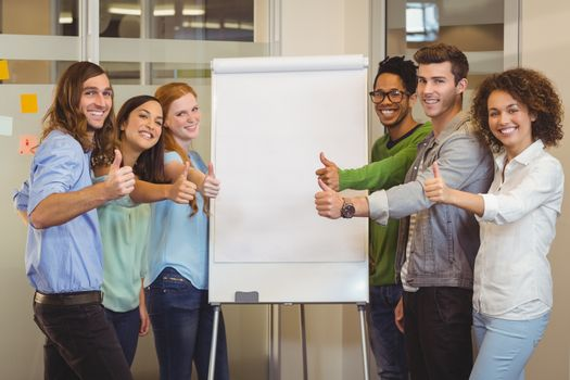 Portrait of smiling business people showing thumbs up white standing by whiteboard during meeting in office
