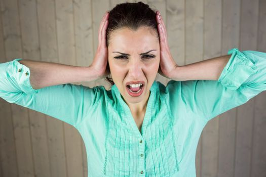 Woman screaming with head in hands