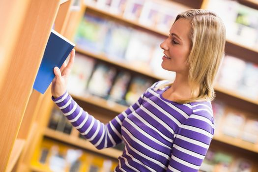 Woman selecting book from bookshelf