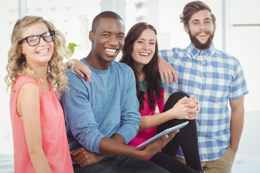 Portrait of cheerful business people with man holding digital tablet in creative office