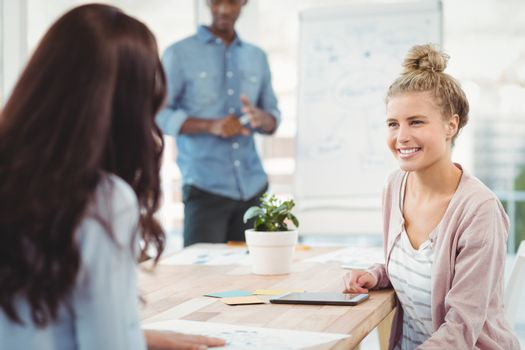 Smiling woman discussing with coworker