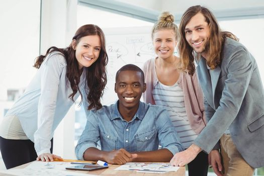 Portrait of smiling business team discussing at desk in creative office