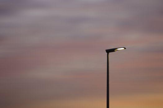 A lantern faces a blurred pink orange sunset.