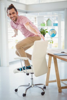Happy businessman standing on swivel chair