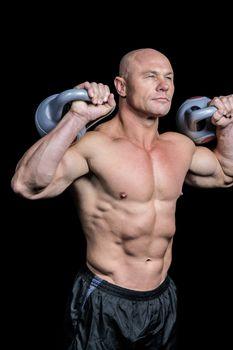 Bodybuilder lifting kettlebells