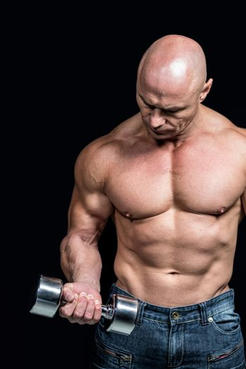 Bald man exercising with dumbbells