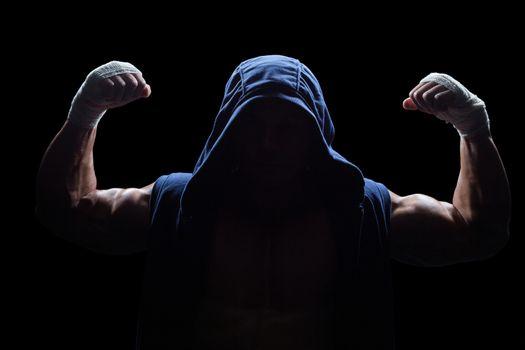 Athlete in hood flexing muscles