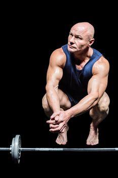 Bodybuilder crouching by crossfit
