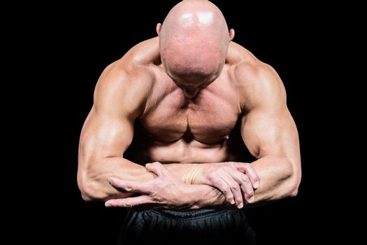 Bodybuilder flexing muscles while looking down
