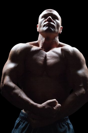 Bodybuilder looking up while flexing muscles