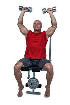 Muscular man exercising while sitting on bench press