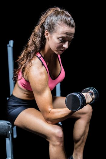 Woman lifting dumbbell while sitting on press bench